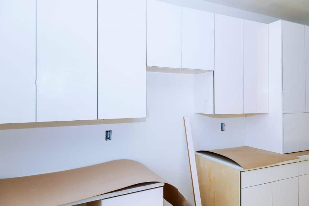 do kitchen cabinets go in before tile flooring